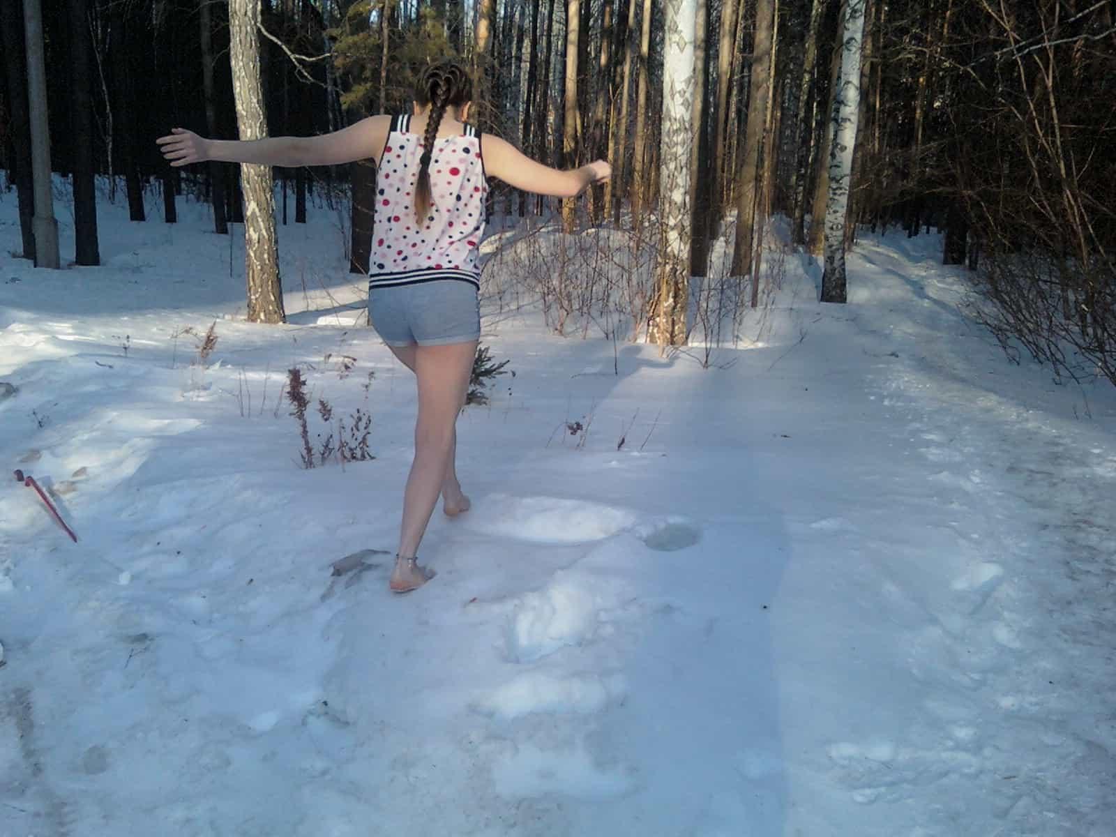 Ребёнок бегает босиком по снегу